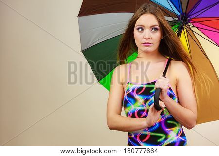 Shy Woman Posing In Swimsuit And Colorful Umbrella