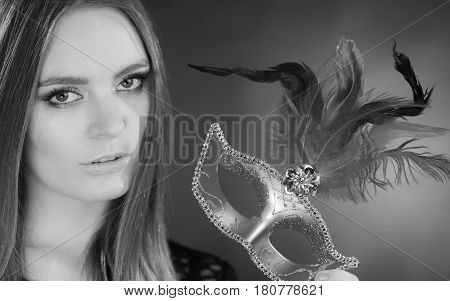 Party time holidays people and celebration concept. Woman long hair holding carnival mask close up. Black & white photo