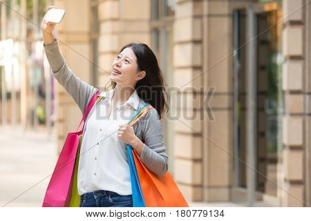 Woman Holding Shopping Bags While Taking Self-portrait