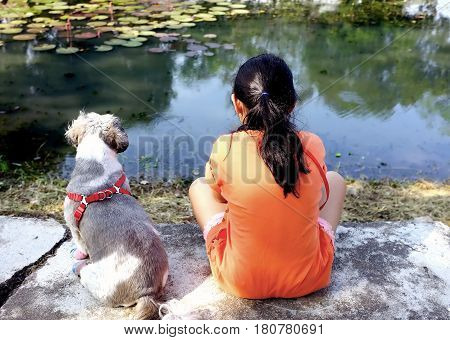 Little girl wearing orange t-shirts and Shih Tzu puppy with red harness natural scenic ride in the park, friendship amidst the serenity of nature