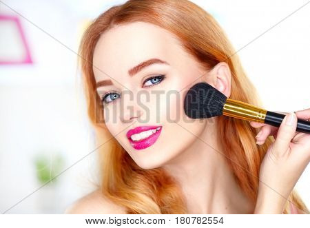 Beauty woman applying makeup. Beautiful girl looking in the mirror and applying cosmetic with a big brush. Girl gets blush on the cheekbones. Powder, rouge. Makeup for redhead woman