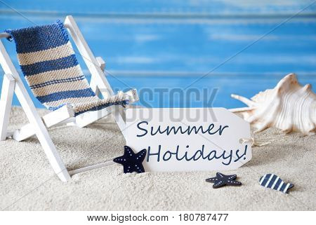 Summer Label With English Text Summer Holidays. Blue Wooden Background. Card With Holiday Greetings. Beach Vacation Symbolized By Sand, Deck Chair And Shell.