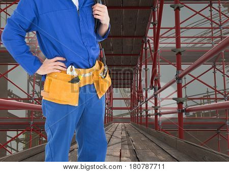 Digital composite of Builder with tools belt in 3D scaffolding