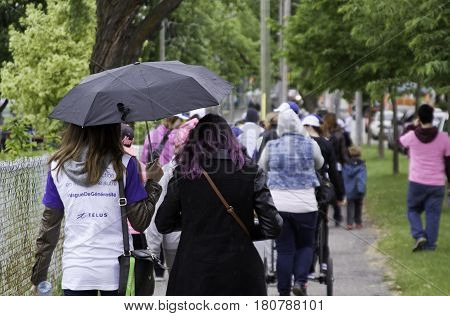 Laval, Quebec - June 12, 2016 - A shot from the back of people walking down a path as it began to rain at the Junior Diabetes Walk in Laval, Quebec on a bright overcast day in June.