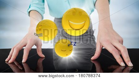 Digital composite of Close up of business woman's hands on table with emojis and flares against blurry blue wood panel