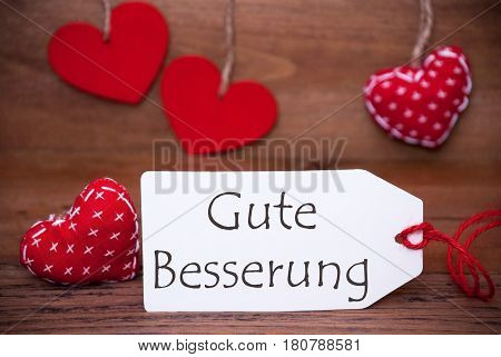 Label With German Text Gute Besserung Means Get Well Soon. White Label With Red Textile Hearts. Retro Brown Wooden Background.