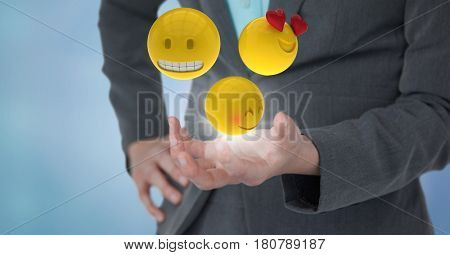Digital composite of Close up of woman's hand with emojis and flare against blue background