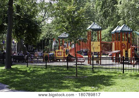 Montreal, Quebec - July 27, 2016 - Wide view up of a colorful children's park with people enjoying the afternoon on a sunny day in a park in Montreal, Quebec in late July.