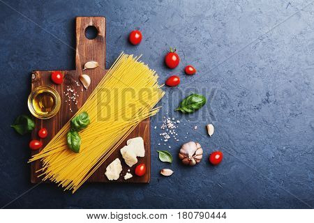 Italian food background with uncooked spaghetti, tomato, basil, cheese, garlic and olive oil on black stone table. Ingredients for cooking pasta with space for recipe. Flat lay.