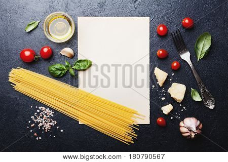 Italian food background with uncooked spaghetti, tomato, basil, cheese, garlic and olive oil on black stone table. Top view in flat lay style. Ingredients for cooking pasta with space for recipe.