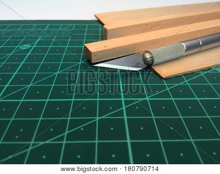 cutting mat with hobby knife and wood strips