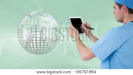 Digital composite of Doctor (men) using his tablet while he looks the 3D metallic earth