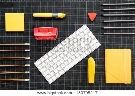 Top View Of White Keyboard And Organized Office Supplies On Black