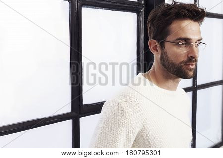Stubble guy in white sweater looking away