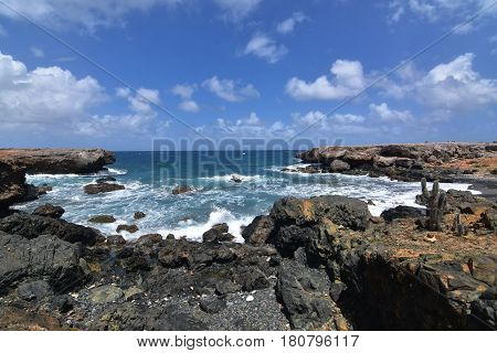 Rugged lava rocks encircling the cove of Aruba's black sand stone beach.