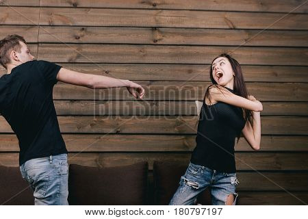 cheerful couple having pillow fight. They wear in black shirt and jeans and stand on bendend knees on the bed. Everyone is holding a pillow