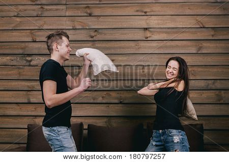 cheerful couple having pillow fight on sofa. They wear in black shirt and jeans and stand on bendend knees on the bed. Everyone is holding a pillow