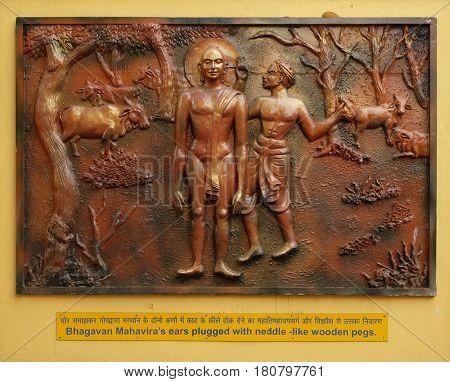 KOLKATA,INDIA - FEBRUARY 09, 2016: Bhagavan Mahaviras ears plugged with neddle - like wooden pegs, Street bass relief on the wall of Jain Temple (also called Parshwanath Temple) in Kolkata, India