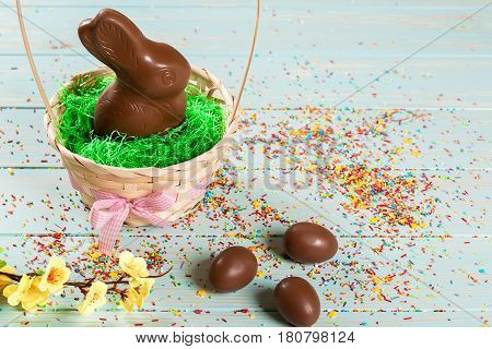 Beautiful Easter Composition With Chocolate Bunny And Eggs In A Wicker Basket With A Bow, Colored Po