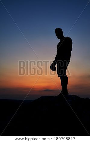 Silhouette of a man standing on top of a rock observing beautiful sunset copyspace anonymous mysterious nature skies sky dusk epic alone person loneliness beauty relaxation vitality harmony.
