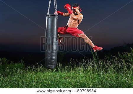 Professional kick boxer jumping and kicking a punching bag with his knee training outdoors on sunset copyspace workout exercising practicing performance preparing competitive motivated