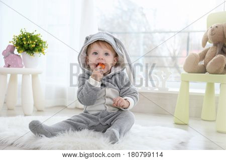 Cute little baby in bunny costume sitting on floor at home and eating carrot