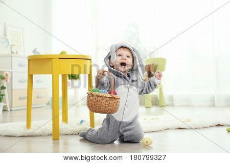 Cute little baby in bunny costume playing with Easter eggs at home