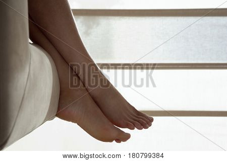 Low section of woman resting with feet up on sofa in living room