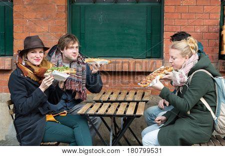 CRACOW POLAND - JANUARY 30 2016: Young people eat Zapiekanka - Polish fast-food a casserole on Plac Nowy in Kazimierz district Krakow. Poland