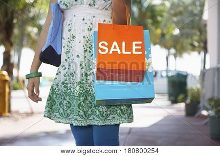 Midsection of teenage girl carrying shopping bags on street with text saying SALE
