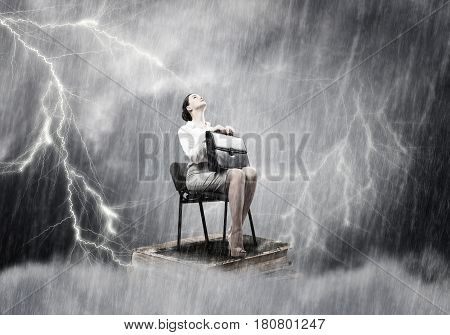 Young businesswoman with suitcase sitting on books under rain