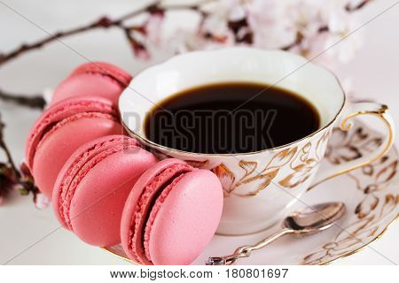 A french sweet delicacy macaroons variety. Cup of black coffee apricot flowers and sweet pastel french macaroons on white wooden table