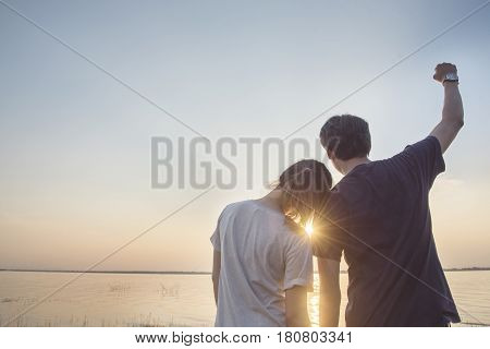 Romantic young asian couple in love sitting on pier during sunset time