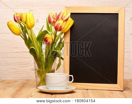 Black board with blank space for text, bouquet of tulips in a vase  and cup of coffee on a wooden table on a light wooden background. Copy space for adding your content. Menu. Advertising