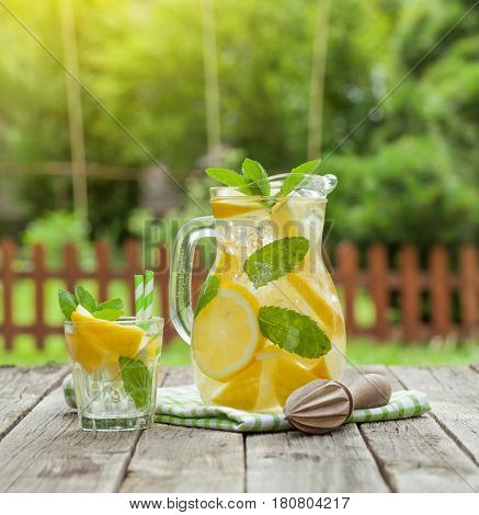 Lemonade pitcher and glass with lemon, mint and ice on garden table