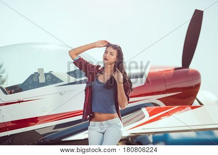 Pilot woman standing at cabin plane outdoors in sunny day. Attractive young multi-racial Asian Caucasian sexy girl in jeans and shirt near wing sport airplane in airport looking at camera.
