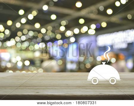 Restaurant cloche flat icon on wooden table over blur light and shadow of shopping mall Food delivery concept