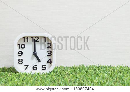 Closeup white clock for decorate in 5 o'clock on green artificial grass floor and cream wallpaper textured background with copy space