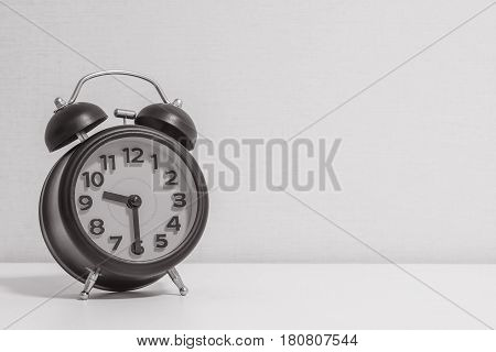 Closeup alarm clock for decorate show half past nine o'clock or 9:30 a.m.on white wood desk and cream wallpaper textured background in black and white tone with copy space