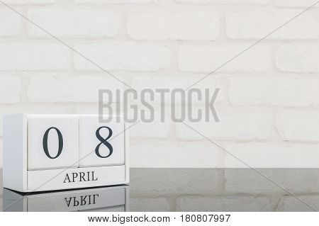 Closeup white wooden calendar with black 8 april word on black glass table and white brick wall textured background with copy space selective focus at the calendar