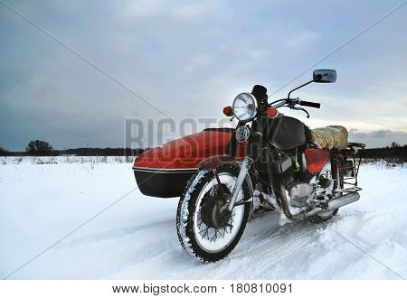 Old motorcycle with sidecar in winter field