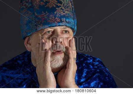 Portrait of anxious senior man in blue oriental clothes against dark background