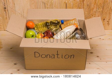 different food in cardboard box with donation sign on wooden table donation concept