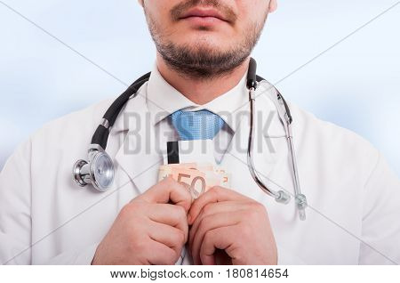 Close-up Of Medical Doctor With Money In Hands
