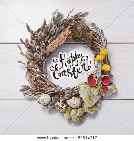 Happy Easter card .Wreath with willow twigs; mushrooms and quail eggs on a white wooden background