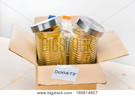 Different Food In Cardboard Box With Donation Sign On Wooden Table On White, Donation Concept