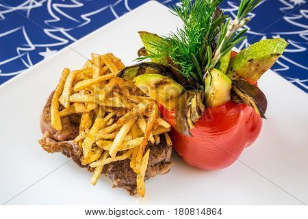 Meat with French fries vegetables and herbs on a white plate