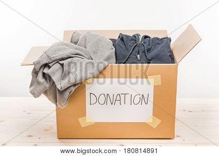 Cardboard Box With Donation Clothes On Wooden Table On White, Donation Concept
