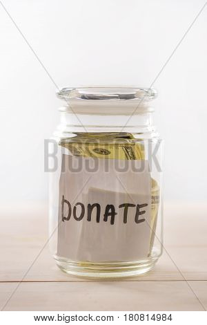 Close-up view of dollar banknotes in glass jar with donate lettering donation concept