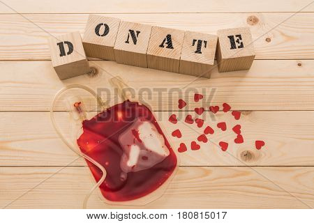 Top View Of Blood Bag And Wooden Cubes With Word Donate, Donation Concept